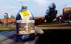 "Large plastic water bottle with poison symbol and ""Muskrat Falls Water: 10% Methylmercury"""
