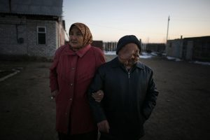 Elderly woman stands arm in arm with elderly man with severe facial deformities