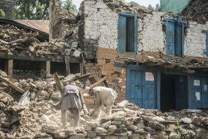 Two men search through stones and materials from a collapsed house from earthquake