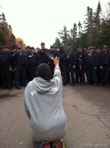 Indigenous woman kneeling on the road holds her hand and a feather toward police walking toward her