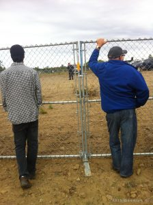 Two people look through a fence