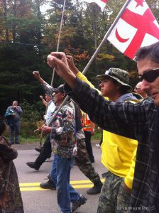 Indigenous people march, carrying flags