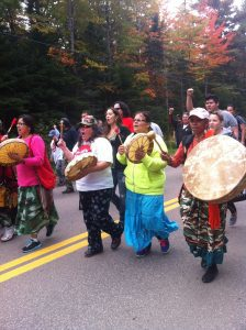 Indigenous people march, sing and play drums