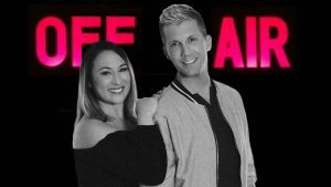 "Radio hosts Jesse and Jenna stand in front of a neon ""Off Air"" sign"