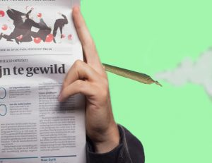 A person reads a newspaper while holding a marijuana cigarette