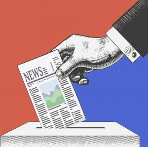 A hand puts a ballot into a box