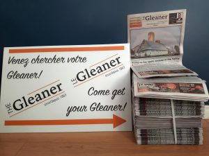 "A white sign reading ""Come get your Gleaner"" in English and French points to a stack of newspapers."
