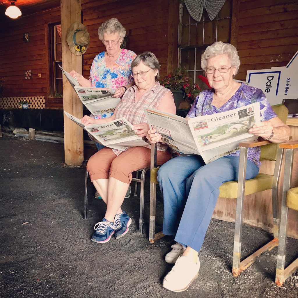 Three older white women, one standing and two sitting on comfy chairs, read copies of The Gleaner paper outside.