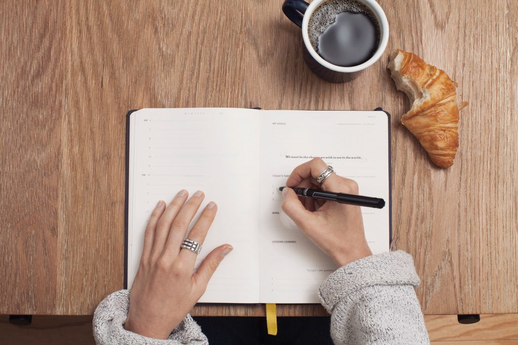 A pair of hands writes in an blank, open planner on a wooden table. There's a cup of coffee on the table as well.