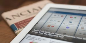 An iPad sits on top of a copy of the newspaper, with a listicle open.