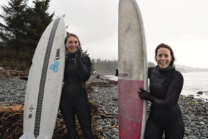 Two women stand with surf boards