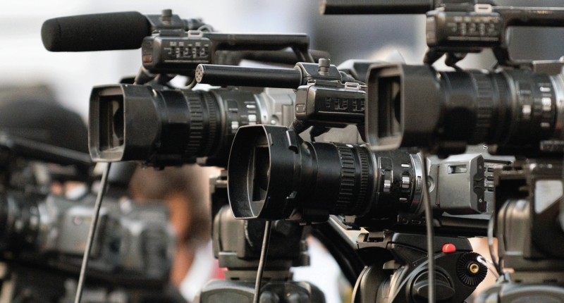 Multiple professional cameras on tripods aiming in the same direction