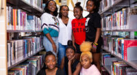 Annette Bazira-Okafor with 6 writers from Black Girls Magazine, all are standing between bookshelves and smiling at the camera