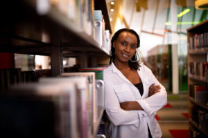 Annette Bazira-Okafor, the magazine's founding editor, leaning on bookshelf while smiling at the camera.