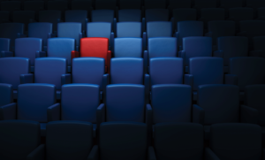 A movie theatre full of blue seat with one red seat standing out on the top left corner