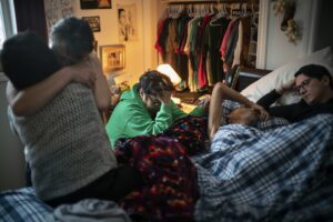 A dying man lays in a bed surrounded by friends and family as he copes with a rare form of bile duct cancer known as cholangiocarcinoma, at his home, in Fort Chipewyan AB.