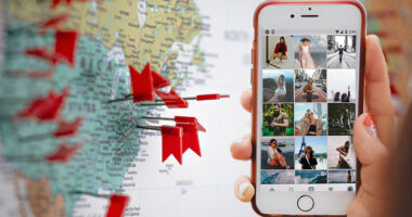 Map with pins in it and a cell phone showing photos of people on vacation
