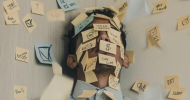A young man lies on the ground, his face covered in sticky notes