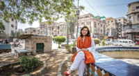 Sanam Maher sits on the ledge of an empty fountain in Pakistan