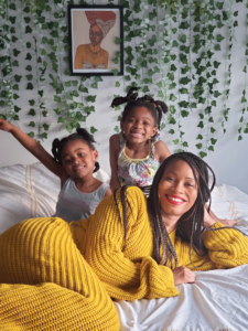 Mother and two young daughters smiling while laying on a bed with greenery in the background.