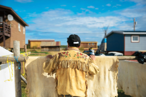 George Cleary, a former Deline chief, wears a jacket made of caribou and looks out over the community while standing against a drying moose hide.