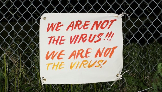 Sign on a fence that says we are not the virus, we are not the virus.